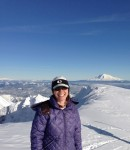 Shannon Wilkinson on the summit of Mt. Saint Helens with Mt. Adams in the background